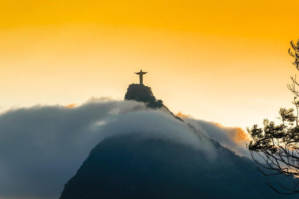 bright yellow and orange sunset and clouds with a silhouette of christ the redeemer statue in rio de Janiero in Brazil, one of the best places to visit in South America