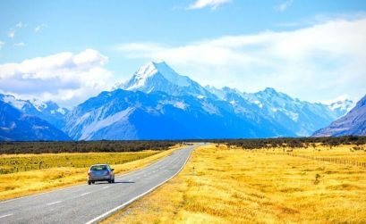 car on road driving to blue mountains with yellow grass next to it road trip quotes