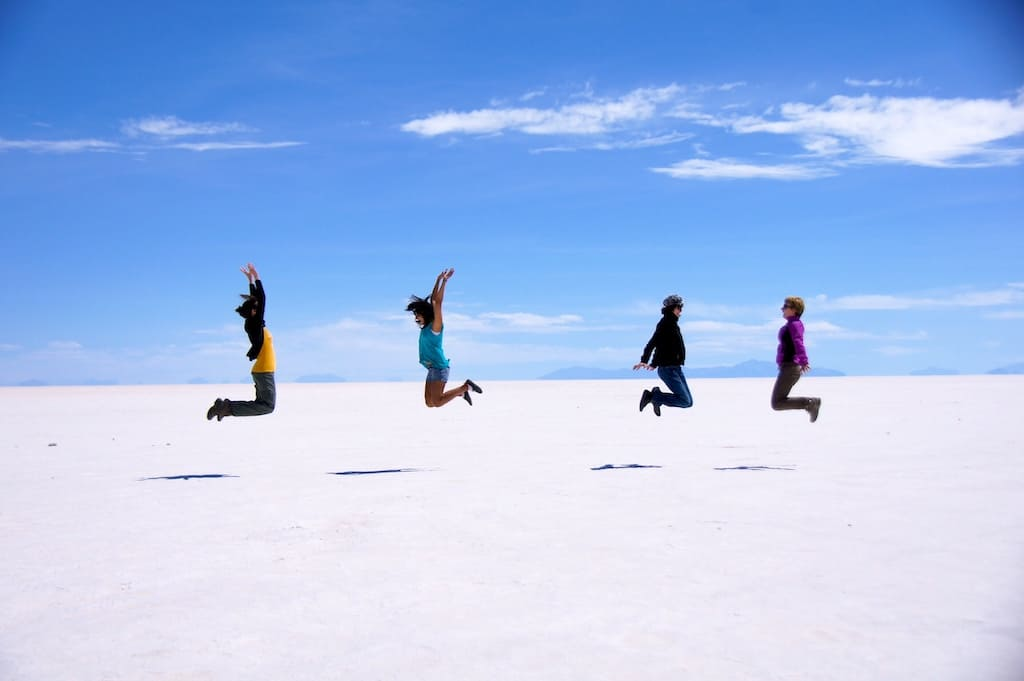 4 people coordinating and jumping in the air with salt flats in the background. white on the ground and blue in the sky