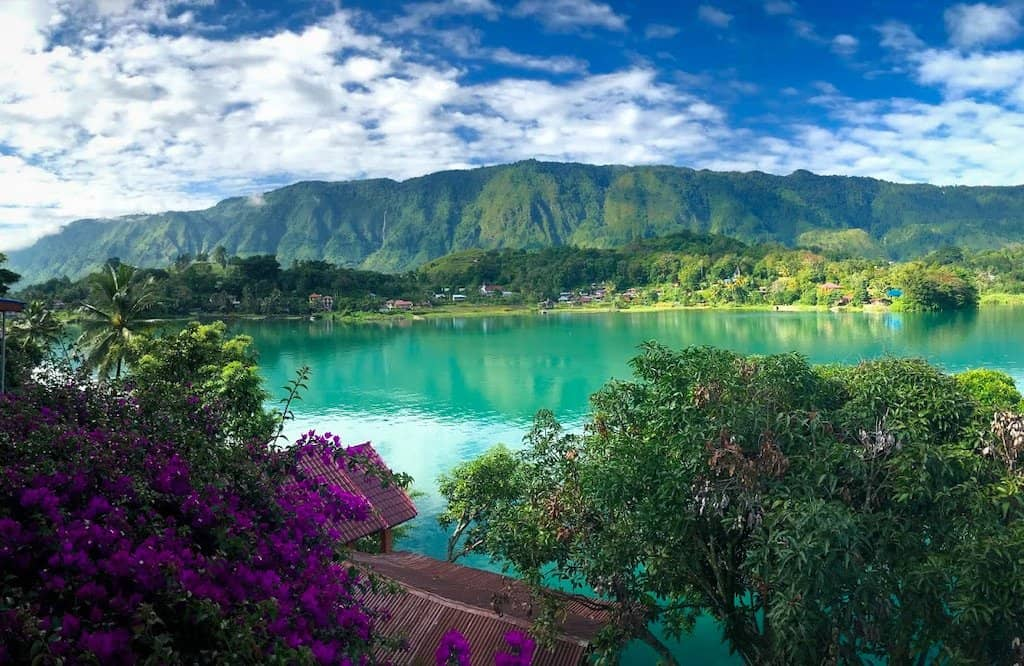 an emerald green lake is surrounded by purple flowers and a green mountain in Samosir island in north Sumatra Indonesia - the beautiful islands in asia