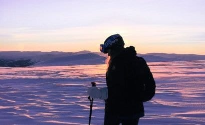 girl skiing under a purple sunset in April