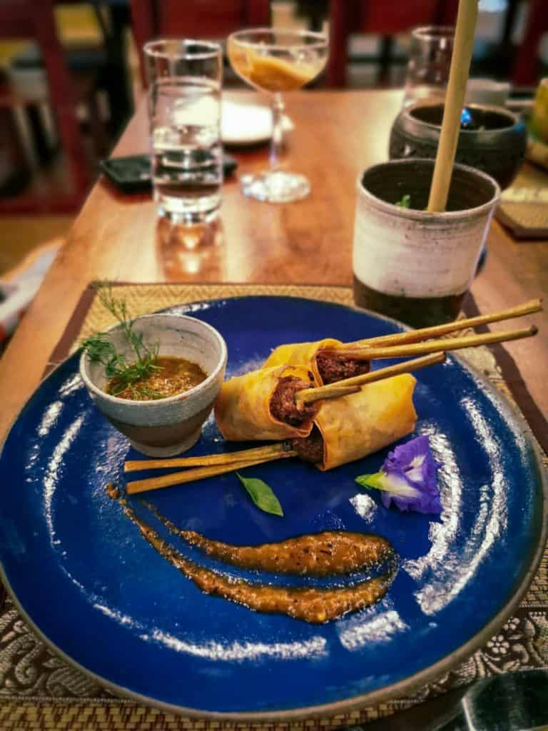 spring rolls on skewer on a blue plate at the spirit house in Luang Prabang laos