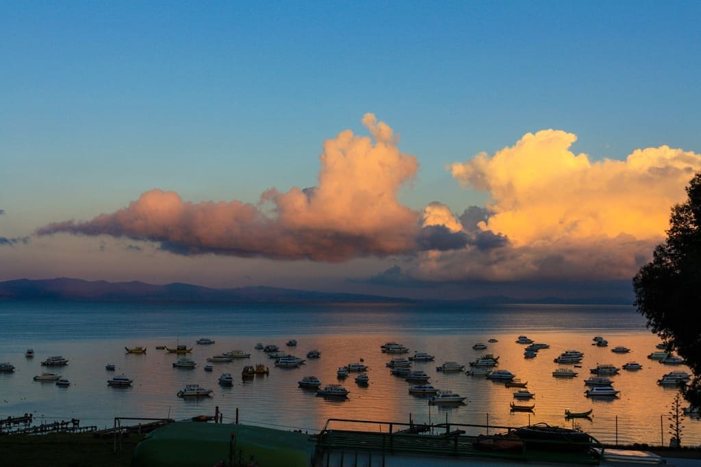 boats on lake with sunrise and golden clouds above in south america