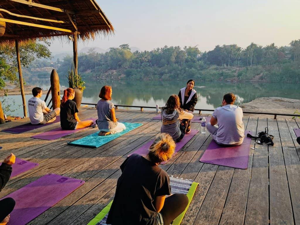 dozen people sit on wooden platform doing an outdoor yoga class infront of nam khan river in luang prabang laos