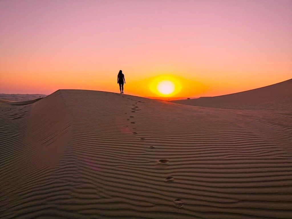 silhouette of a woman walking in pink sunset on sand dune in desert safari Abu Dhabi