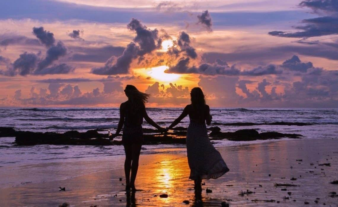 two girls walk on beach holding hands with purple sunset in background and they are silhouettes, sunset captions would be fitting for this picture