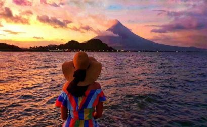 Girl in stripey colourful dress and sun hat sits in front of mayon volcano with a pink sunset in legazpi philippines