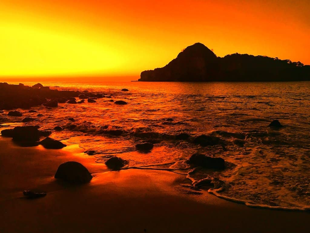 orange sunset on beach with waves crashing in and silhouette of rocks and islands in the background in Redonda bay nicaragua