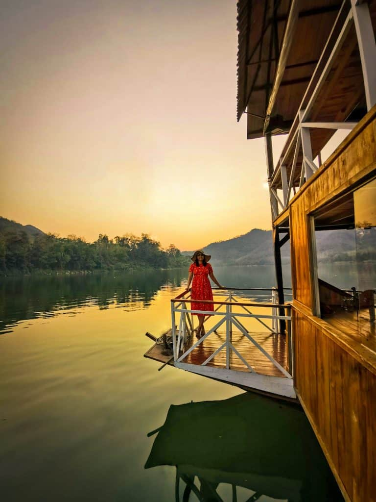 girl in red dress stands on river boat with sun setting behind on the Mekong river with still waters in Luang Prabang laos