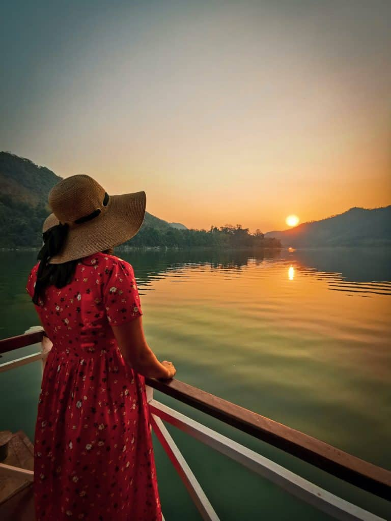 girl in red dress looks over at the sun setting on the Mekong river with still waters in Luang Prabang