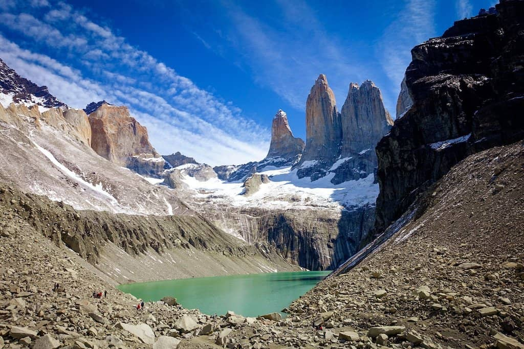 3 limestone towers in a mountain range with a green lake underneath in Patagonia, in Torres del Paine national park in Chile, one of the best hikes in South America