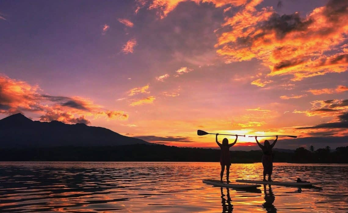 two women holding stand up paddle board paddles in the air on a lake with pink and orange sunset