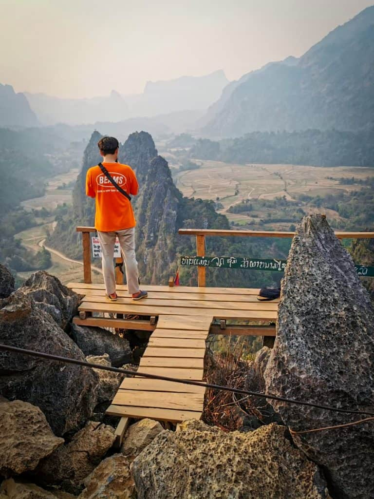 man in orange t-shirt stands on wooden platform at the top of a mountain in nam xay Vang Vieng Laos