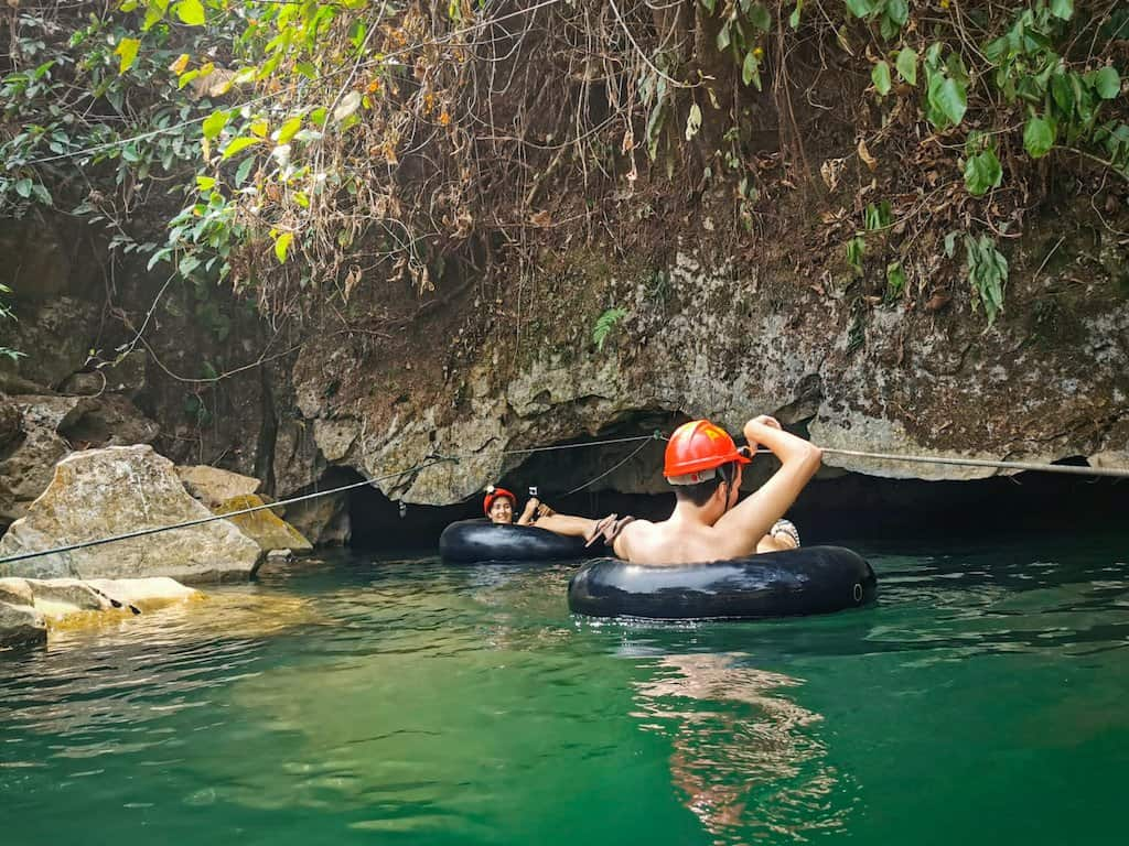 2 people in tube and helmets are in green water going into an underwater cave in vang vieng laos