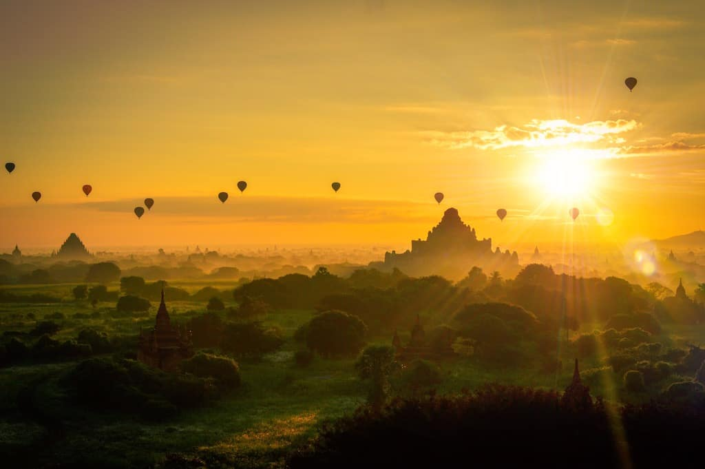 sunrise views of temples in the distance and green countryside with the yellow sky filled with the silhouette of 12 bagan hot air balloon