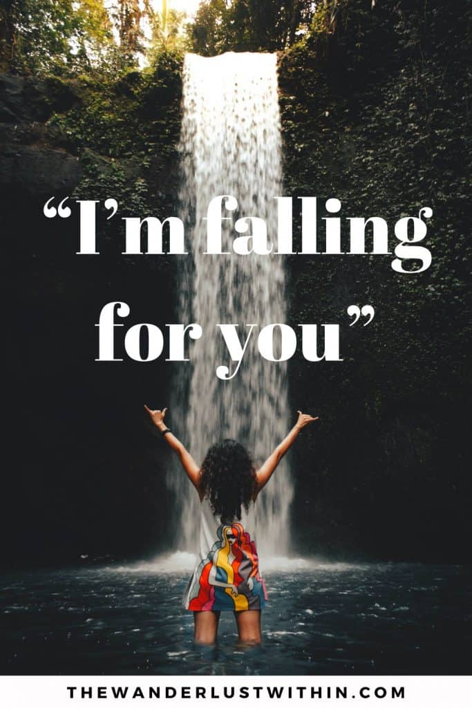 "girl stands with arms in air looking up at a wild waterfall with a waterfall quote saying ""I'm falling for you"""