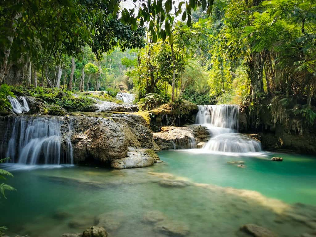 photo of cascading waterfalls and emerald waters with a jungle in the background in laos. it is called Kuang Si waterfalls as is one of the best things to do in Luang Prabang