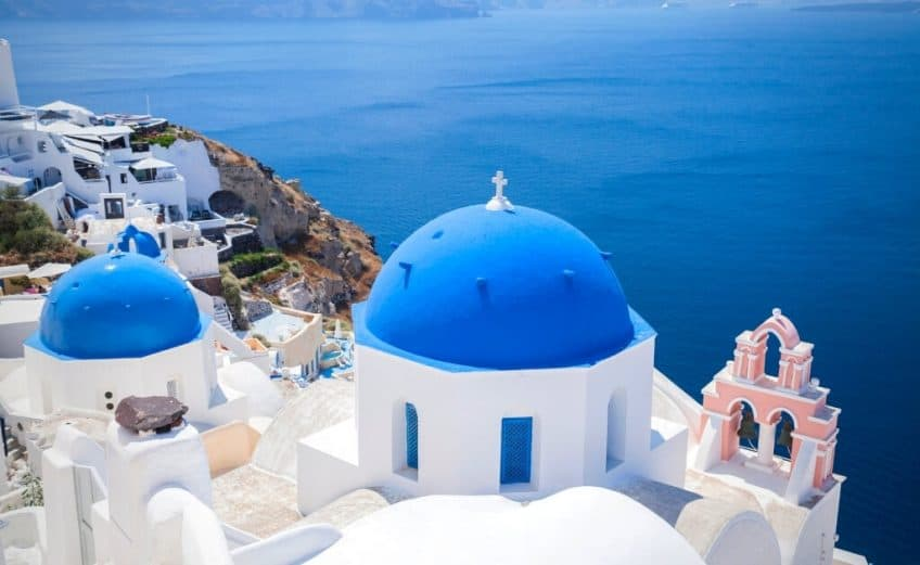 blue rooftops and white buildings in oia santorini greece which has some beautiful cave hotels and airbnbs in santorini