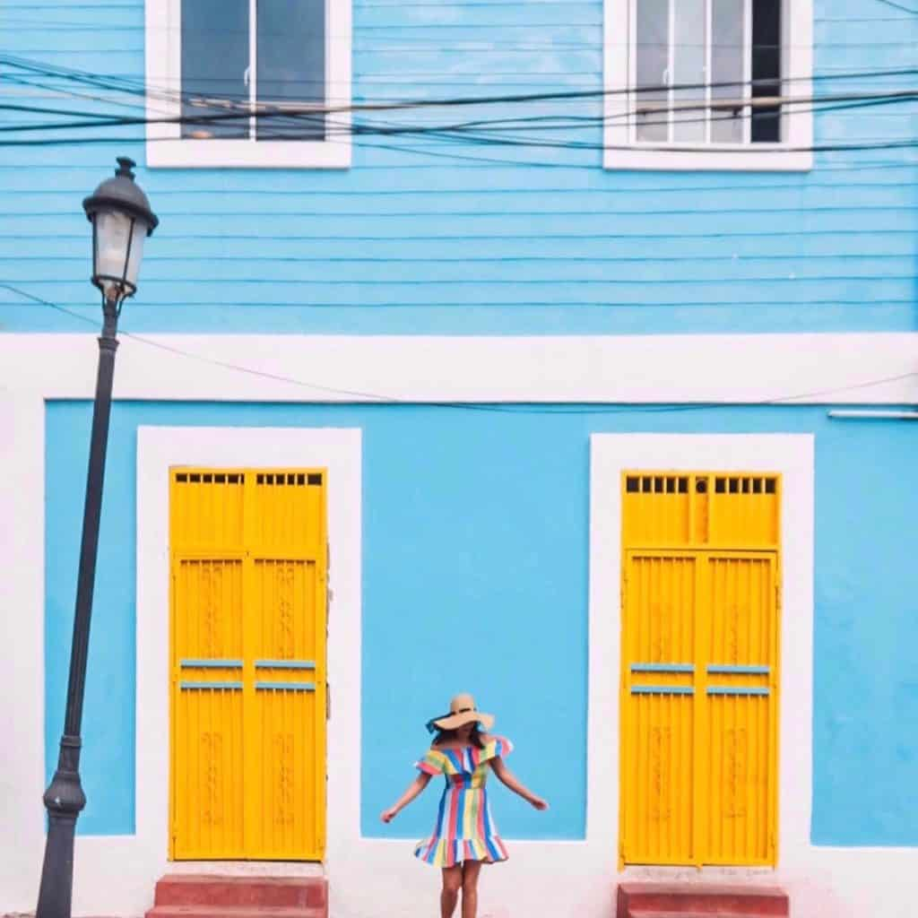 two yellow doors with a baby blue building and a girl twirling in a dress in the middle of the symmetrical doors