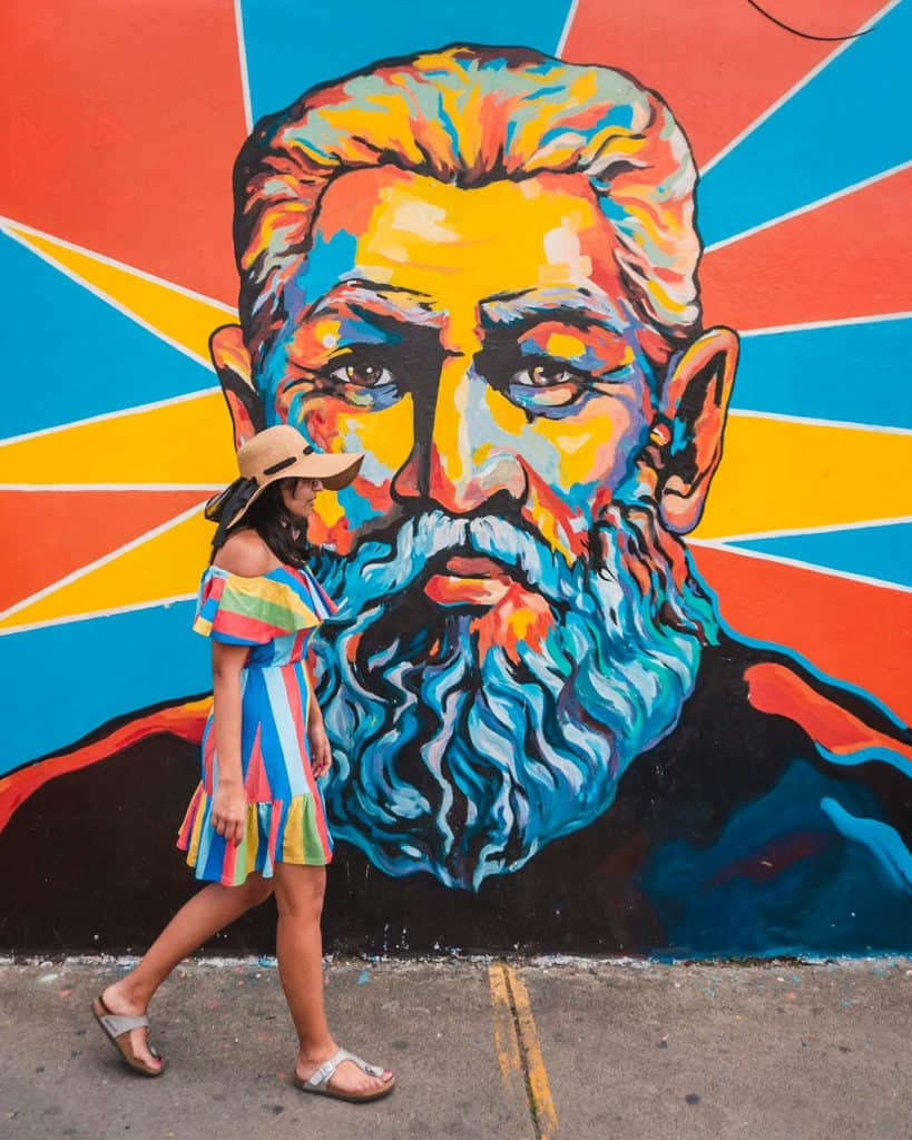 woman in colourful striped dress walks past a mural made up of orange, blue and yellow paint of a man with a beard. the painting colours match the girls dress