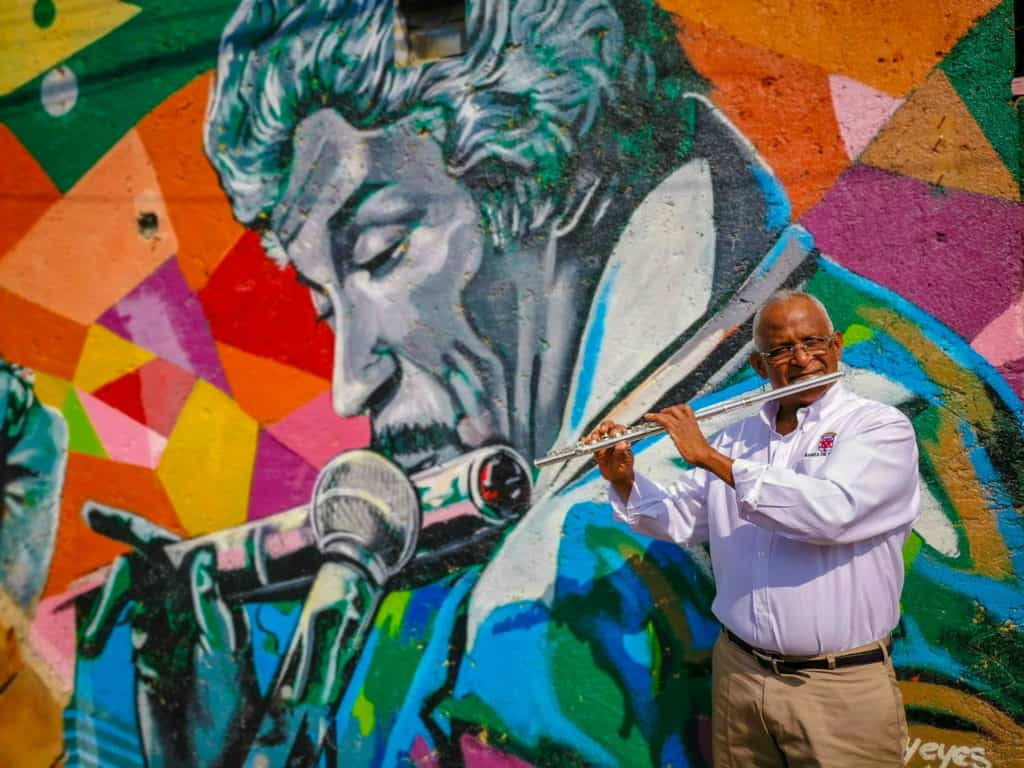 man with flute plays instrument infront of a colourful wall mural of a man playing a flute