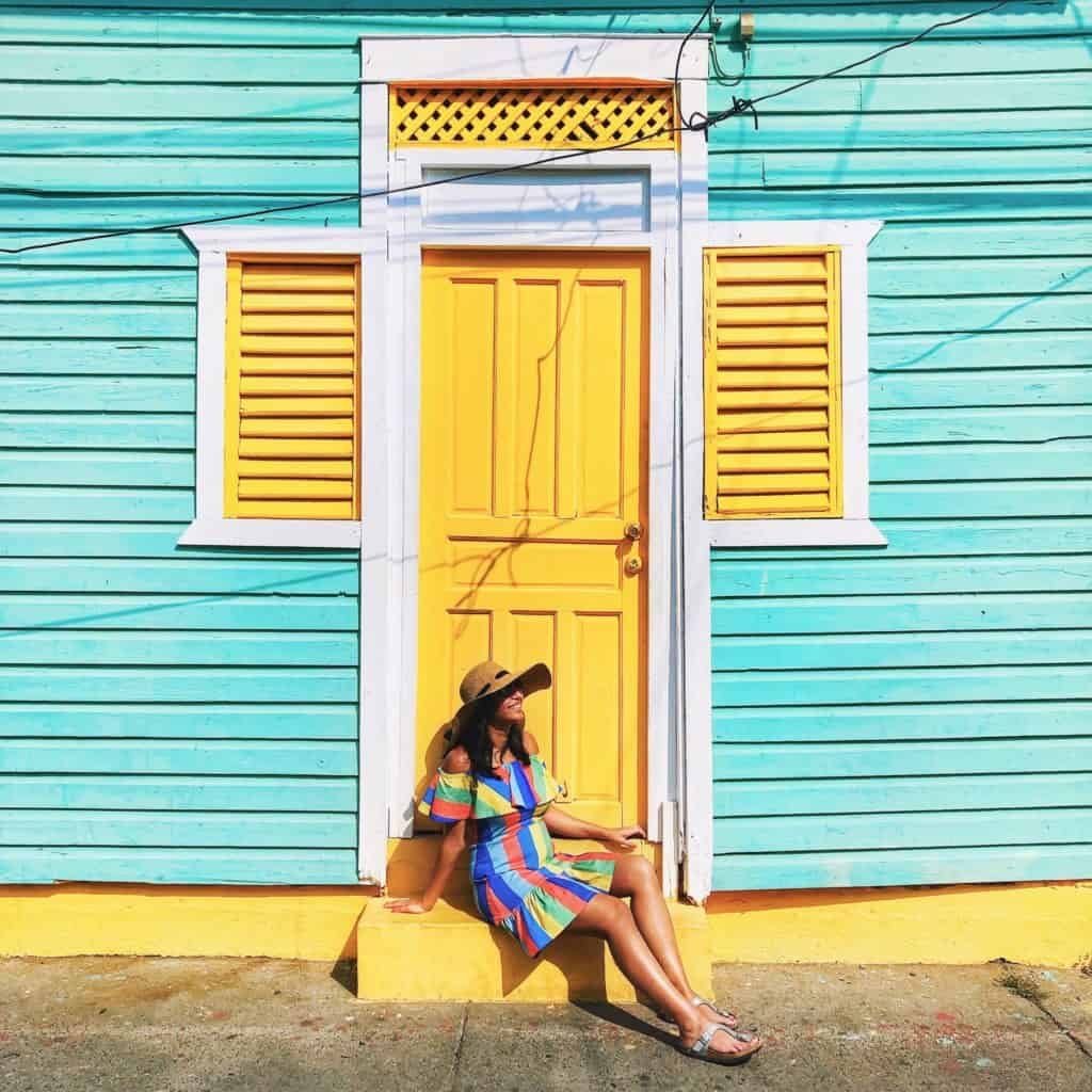 girl in sunhat and stripey colourful dress sits on a doorstop of a blue wooden building with a bright yellow door in los pepinos in Santiago de los caballeros in the Dominican Republic