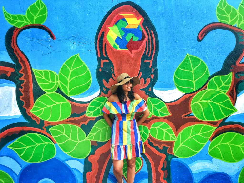 girl in striped dress stands infront of a colourful octopus street art mural