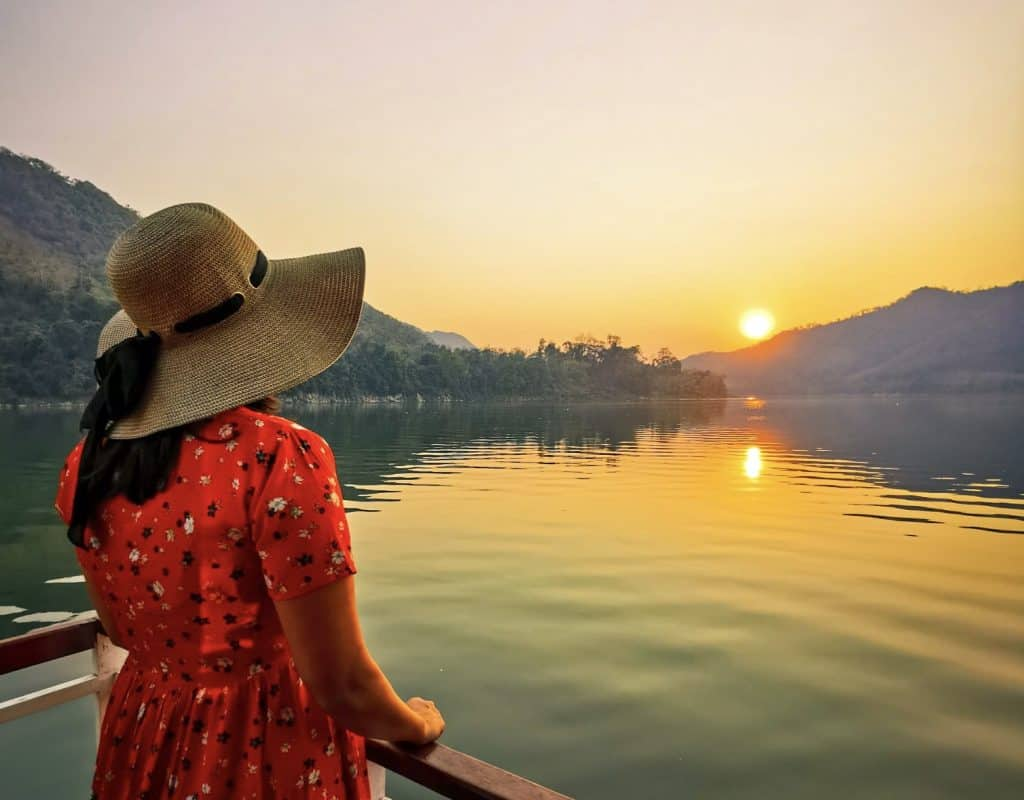 woman in red dress and hat looking at sunset over a river in laos luang prabang, perfect for a sunset caption or quote for instagram